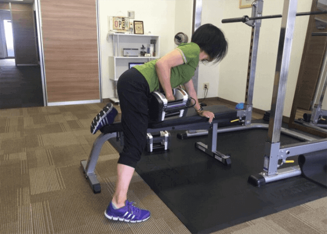 ワンハンドローイングを行なう女性トレーナー松井香